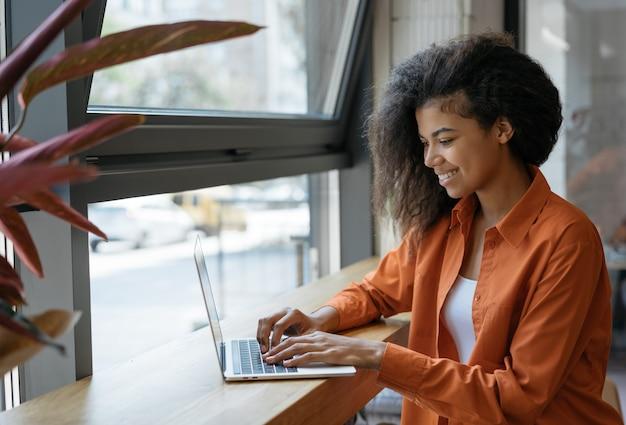 Gelukkige afrikaanse amerikaanse vrouwenschrijver die freelance project van huis werken. zakenvrouw met behulp van laptop, informatie zoeken op website. succesvol bedrijf. online trainingen concept
