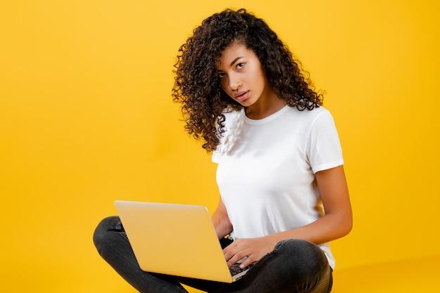 Gelukkige afrikaanse die zwartezitting met laptop over geel wordt geïsoleerd