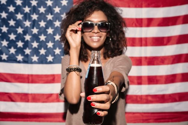 Gelukkige afrikaanse jonge dame die zonnebril draagt