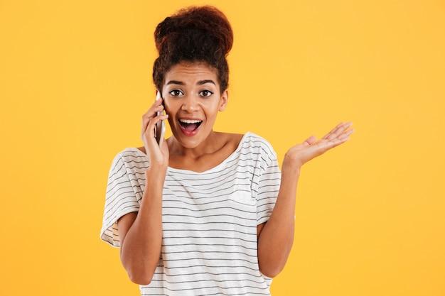 Gelukkige afrikaanse jonge vrouw met het open mond geïsoleerd spreken op telefoon