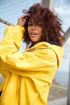 Gelukkige afrikaanse krullende jonge dame die gele laag draagt
