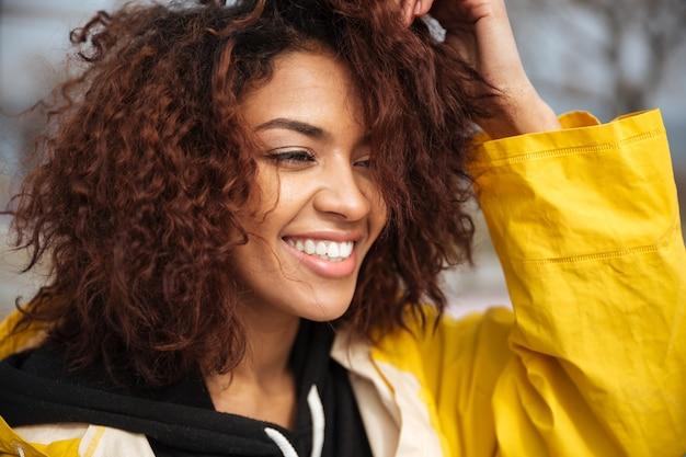 Gelukkige afrikaanse krullende jonge vrouw die gele laag draagt