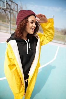 Gelukkige afrikaanse krullende jonge vrouw die het gele laag lopen dragen