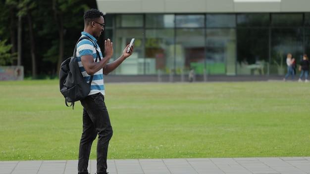 Gelukkige afrikaanse man die videogesprek met een vriend online praat op de mobiele telefoon in de stedelijke straat