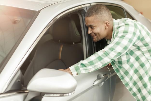 Gelukkige afrikaanse mens die binnen een nieuwe auto het handel drijven bekijken.