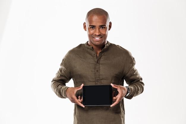 Gelukkige afrikaanse mens die het lege tabletcomputer scherm en kijken tonen