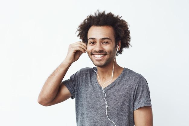 Gelukkige afrikaanse mens die hoofdtelefoon het glimlachen dooft.