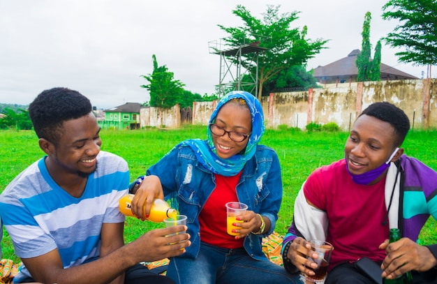 Gelukkige afrikaanse vrienden die drank in hun beker veranderen - vriendschapsconcept