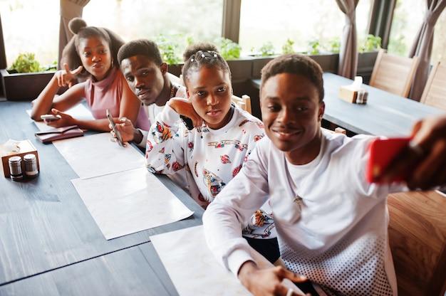 Gelukkige afrikaanse vrienden zitten en chatten in café. groep zwarte volkeren die in restaurant samenkomen en hun mobiele telefoon bekijken.
