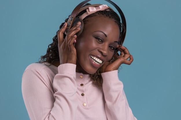 Gelukkige afrikaanse vrouw die aan muziek op hoofdtelefoons luistert