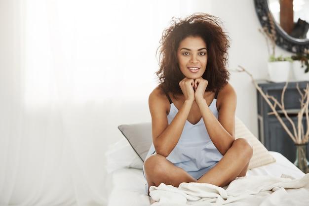 Gelukkige afrikaanse vrouw in nachtkledingzitting op bed die thuis glimlachen.
