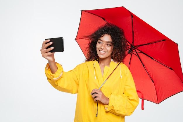 Gelukkige afrikaanse vrouw in regenjas die onder paraplu verbergen en selfie op smartphone over witte achtergrond maken