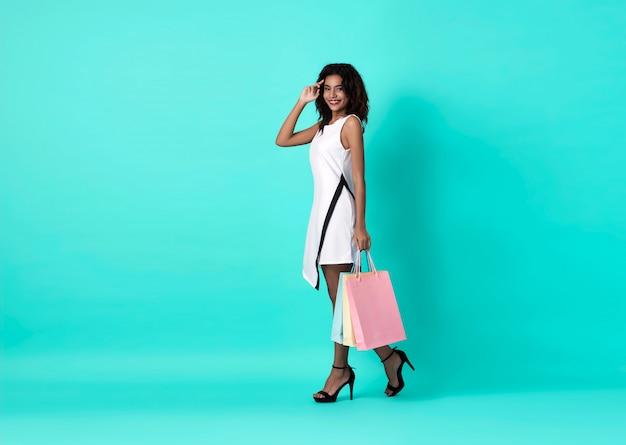 Gelukkige afrikaanse vrouw in witte kleding en handholding het winkelen zak op blauwe achtergrond