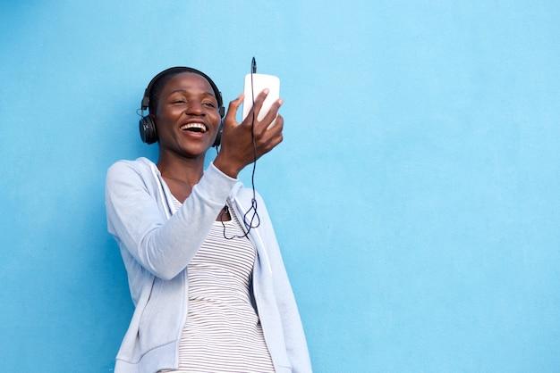 Gelukkige afrikaanse vrouw met slimme telefoon en hoofdtelefoons