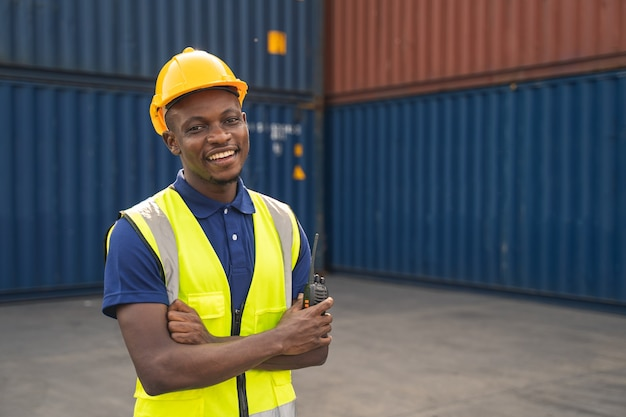 Gelukkige afrikaanse werknemer smailt, staat op de containerwerkplek en gekruiste armen met een gevoel van geluk