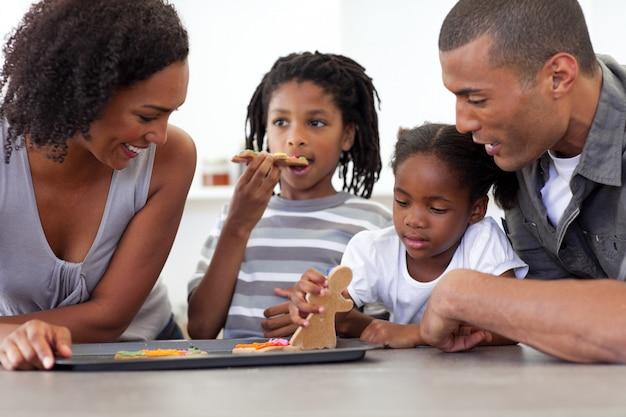 Gelukkige afro-amerikaanse familie die eigengemaakte koekjes eet