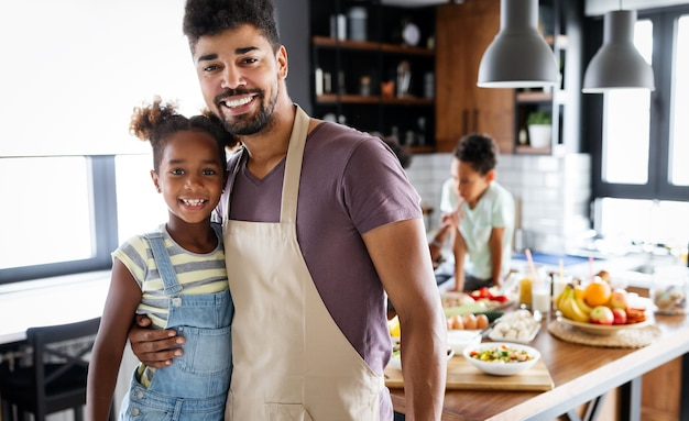 Gelukkige afro-amerikaanse familie die samen gezond biologisch voedsel bereidt in de keuken