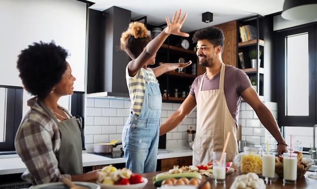 Gelukkige afro-amerikaanse familie die samen gezond voedsel in de keuken bereidt