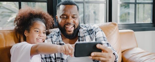 Gelukkige afro-amerikaanse familie, vader en dochter die plezier hebben en een videogesprek met een mobiele telefoon gebruiken op de bank in huis.