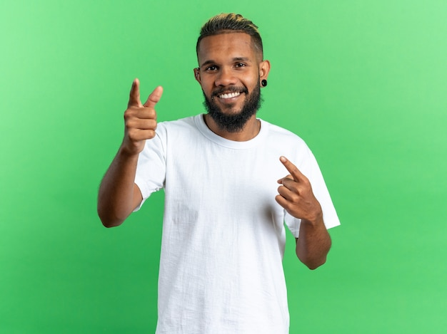 Gelukkige afro-amerikaanse jongeman in wit t-shirt kijkend naar camera glimlachend vrolijk wijzend met wijsvingers naar camera