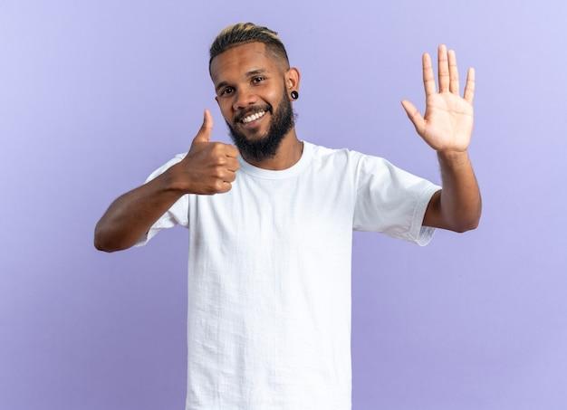 Gelukkige afro-amerikaanse jongeman in wit t-shirt kijkend naar camera zwaaiend met de hand die duimen omhoog laat zien en vrolijk glimlacht