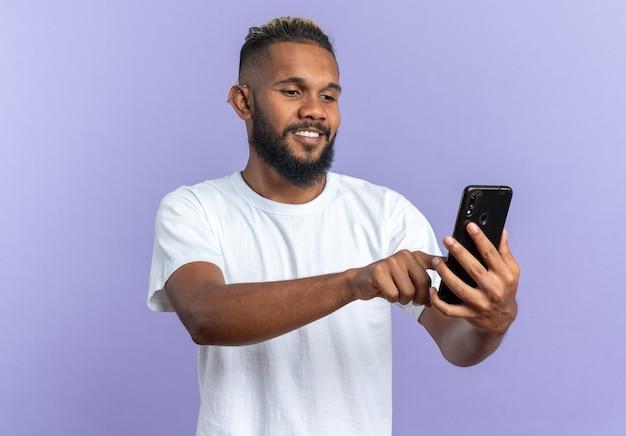 Gelukkige afro-amerikaanse jongeman in wit t-shirt met smartphone die ernaar kijkt en een bericht schrijft met een vrolijke glimlach