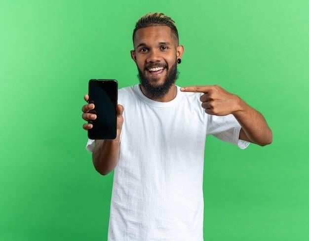 Gelukkige afro-amerikaanse jongeman in wit t-shirt met smartphone die met wijsvinger erop wijst terwijl hij naar de camera glimlacht