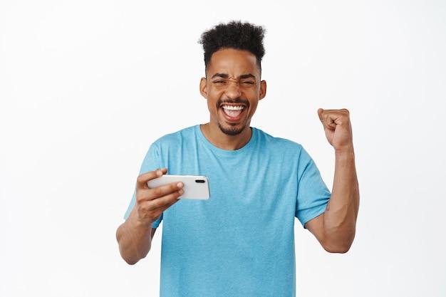 Gelukkige afro-amerikaanse man die wint op videogame op mobiele telefoon, zingen en vieren, opgetogen schreeuwen, glimlachen, smartphone-app gebruiken op wit