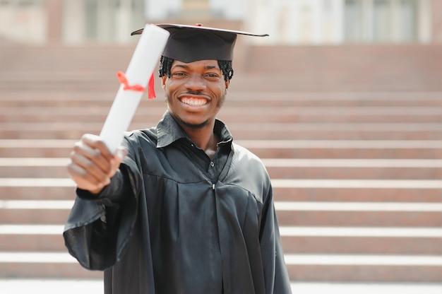 Gelukkige afro-amerikaanse mannelijke afgestudeerde bij ceremonie