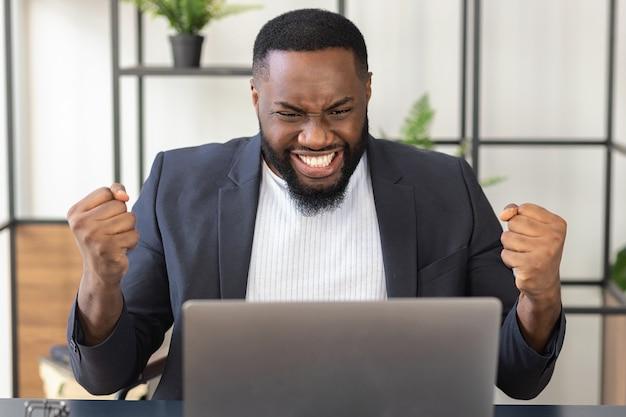 Gelukkige afro-amerikaanse mannelijke zakenman in pak die gelukkig naar de laptop kijkt, een goed bericht kreeg of een goede deal maakte