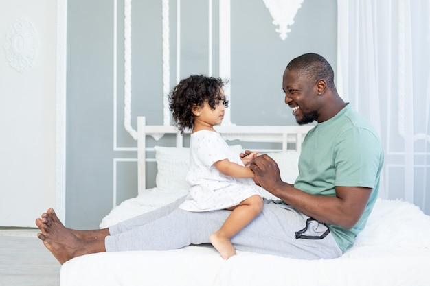 Gelukkige afro-amerikaanse vader en dochter lachend op het bed thuis, gelukkige familie