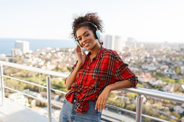 Gelukkige afro amerikaanse vrouw die van mooie muziek geniet door oortelefoons, gekleed in geruit overhemd, die zich op dak bevinden. stedelijk landschap achtergrond.