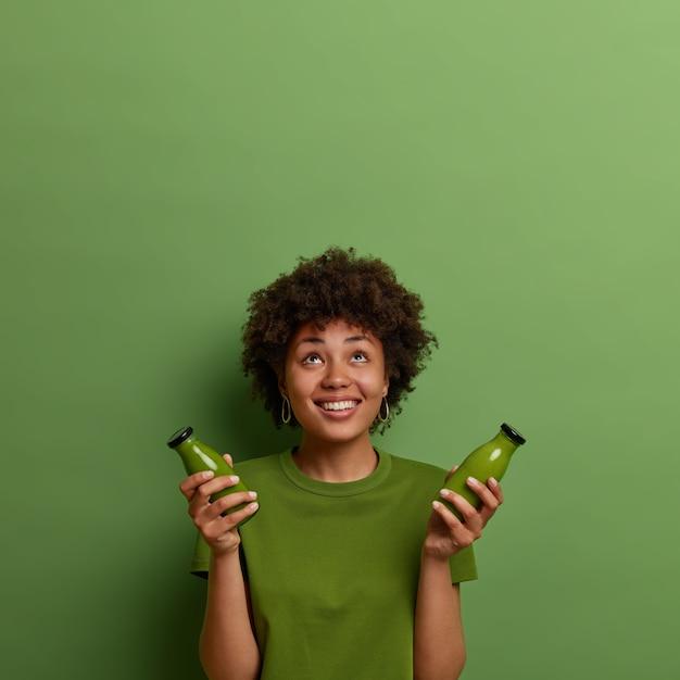 Gelukkige afro-amerikaanse vrouw houdt koude, gezonde gemengde drank vast, boven geconcentreerd, drinkt groene veganistische groentensmoothie, in goede conditie, geconcentreerd boven, lacht aangenaam. superfood concept