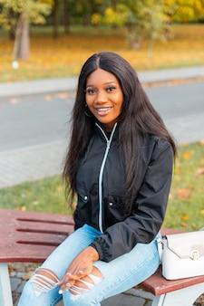 Gelukkige afro-amerikaanse vrouw met glimlach in trendy vrijetijdskleding met jas, jeans en handtas zittend op een bankje buitenshuis