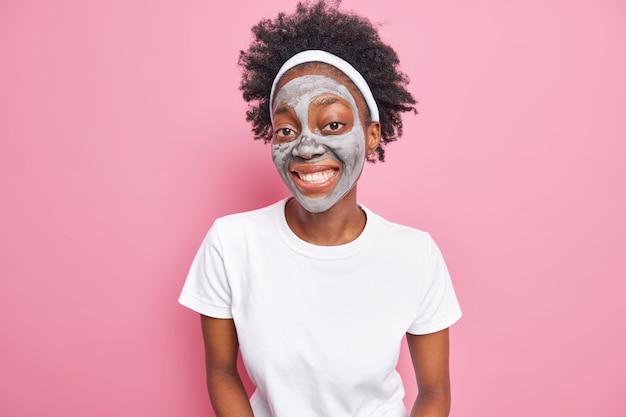 Gelukkige afro-amerikaanse vrouw met krullend haar glimlacht graag schoonheidsbehandelingen en past schoonheidskleimasker toe
