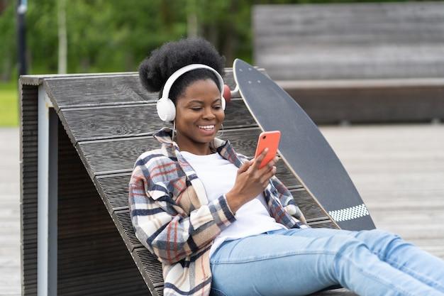 Gelukkige afro-amerikaanse vrouw met skateboard-chat op smartphone zit in het skatepark en sms't buitenshuis