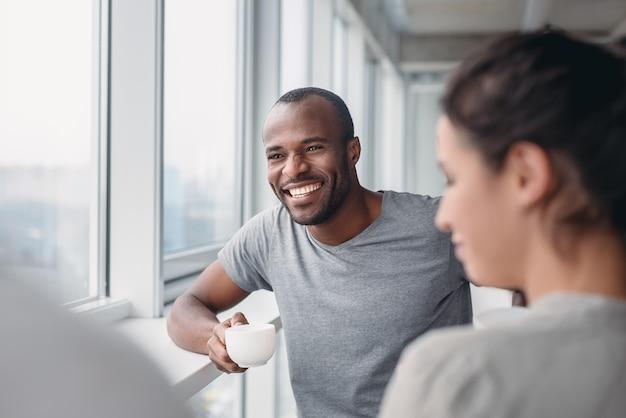 Gelukkige afro-amerikaanse werknemer heeft plezier tijdens de koffiepauze op kantoor, opgewonden mannelijke werknemer lacht om grap van collega's, multiraciale collega's glimlachen onderhandelen. teambuilding concept