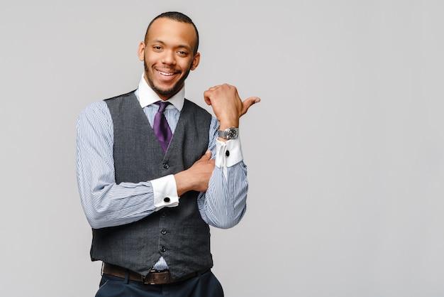 Gelukkige afro-amerikaanse zakenman die zijn duim met glimlach over grijze muur toont