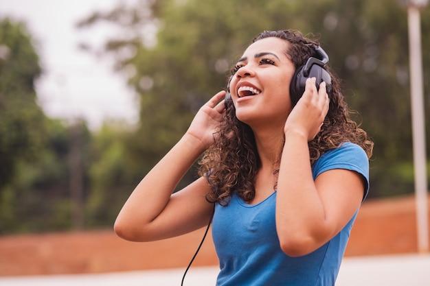 Gelukkige afrovrouw die aan muziek op haar hoofdtelefoon luistert.