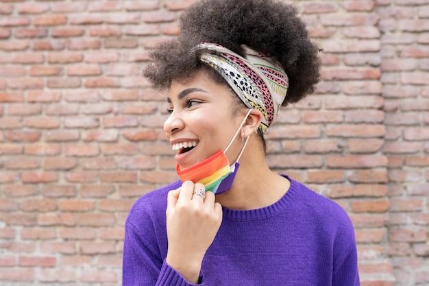 Gelukkige afrovrouw met regenbooggezichtsmasker