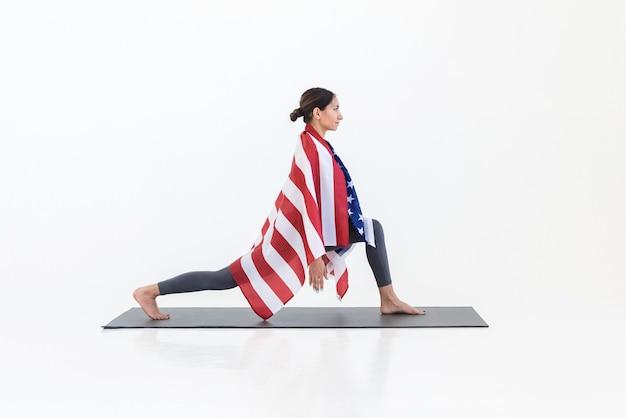 Gelukkige amerikaanse vrouw yogi doen stretching yoga-oefeningen permanent op mat, met amerikaanse vlag, op witte scène in studio. 4 juli amerika onafhankelijkheidsdag concept