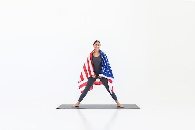 Gelukkige amerikaanse yogivrouw die zich op mat bevindt en voorzijde op witte scène bekijkt. 4 juli onafhankelijkheidsdag concept