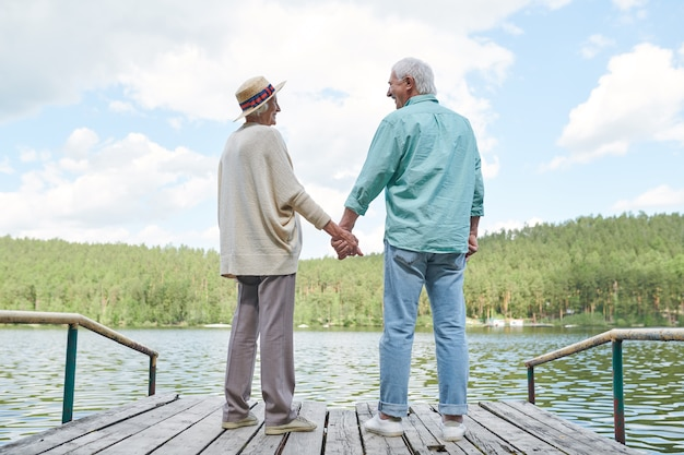 Gelukkige amoureuze senior echtgenoten in vrijetijdskleding kijken elkaar terwijl ze genieten van rust aan het water op zomerdag