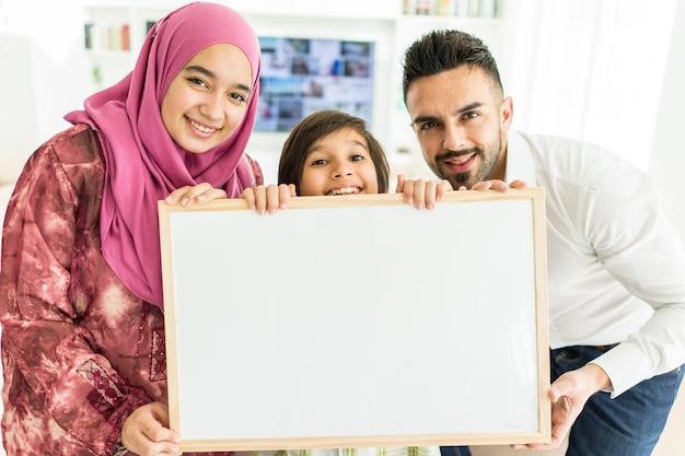 Gelukkige arabische moslimfamilie bij modern huis die pret en goede tijd hebben samen