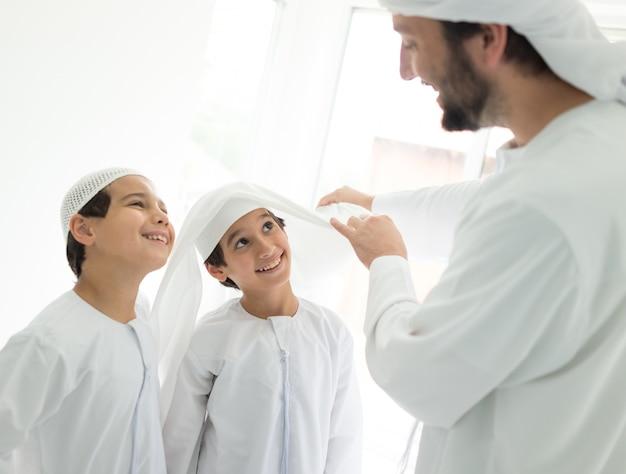 Gelukkige arabische vader die hoofddoek maakt aan zijn zoon