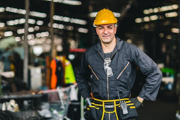 Gelukkige arbeider, de knappe arbeid van de portretglimlach met de riem van veiligheidspakhulpmiddelen en de radiodienstmens in fabriek.