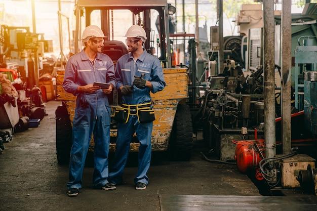 Gelukkige arbeider, die in zware industrie spreken die samen glimlachend glimlachen.