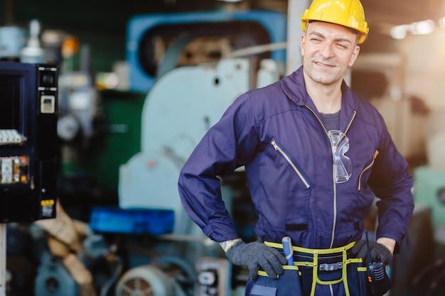 Gelukkige arbeider. ingenieur die voor de machine van de de dienstonderhoud van het de dienstonderhoud in zware industrie met veiligheidspak en helm glimlachen.