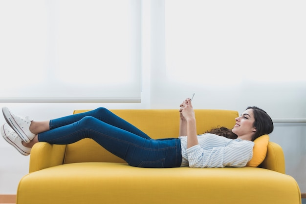 Gelukkige arbeider liggend op de bank en het gebruik van haar mobiele telefoon
