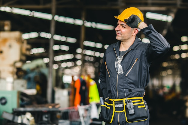 Gelukkige arbeider, portret knappe arbeid met de veiligheidsgordel van veiligheidspak en radiodienstmens in fabriek.